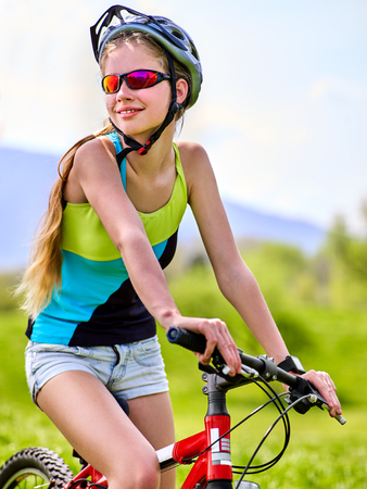 Woman traveling bicycle in summer park. Womens road bike for running on green grass aganist blue sky with white clouds. Cycling trip is good for health. Female in school trip. Stock Photo
