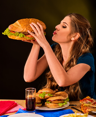 school cafeteria: Woman eating french fries and hamburger with pizza. Student consume fast food on table. Girl trying to eat junk on dark background. Cook teaches cook and shares recipes. Girl suffering from gluttony. Stock Photo