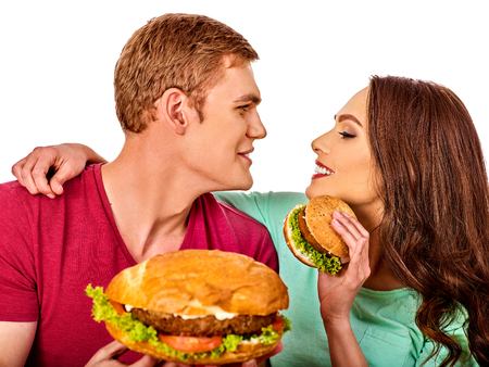beefburger: Couple eating fast food. Man and woman eat hamburger with ham. Friends holding burders junk on isolated. Loving couple prefers fast food to homemade dinner. Use of semi-finished products.