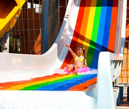 Swimming pool slides for children on water slide at aquapark . Summer kid holiday outdoor. Happy little girl with super gesture in aqua park slide out on inflatable ring.