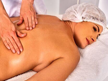 luxacion: Masaje terapeuta mujer haciendo terapia manual de nuevo. Manos de masajista cerca. Tratamiento de las lesiones de la columna vertebral 40 cliente de edad en el salón de spa. Dirección de dislocación en buena clínica. Foto de archivo