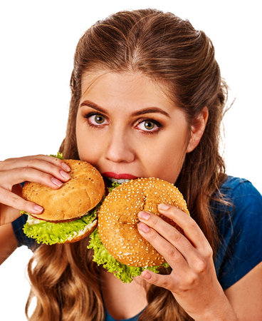 Woman eating hamburgers. Portrait of student consume fast food on table. Girl trying to eat junk against diets. One burger is more delicious than other. Stock Photo
