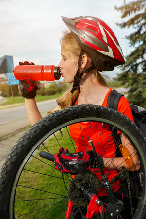 Bicycle tire pumping by bicyclist. Girl repair bicycle and drink bottle water on road . Kids pump up tire. Children return home from school on bicycles. Tone image.