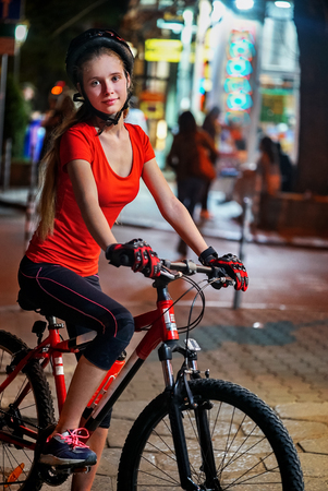 City night bicycle ride. Girls wearing bicycle helmet. Nightlife and passer people in city background.