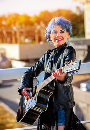 openair: Guitar outdoor music. Woman perform in park outdoor. Girl performing jazz on city street . Spring outside with blue hairstyle background.