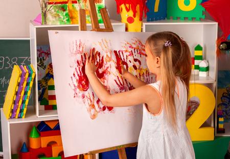 Dito della pittura del bambino sulla cavalletta. Ragazza imparare la vernice nella scuola di classe. Interni dell'aperto sullo sfondo. Immagine con stampe di mani per bambini. Creatività bambini gratis. Archivio Fotografico - 81114962