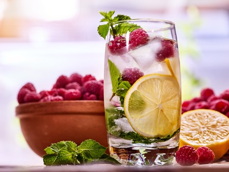 Cold water with lemon and mint leaf. Fresh raspberries lemonade with lime slice and ice cubes. Nonalcoholic beverage in misted glass of ice cocktail glass on wooden board. Table setting rural style. Stock Photo