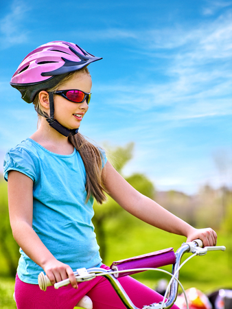Child traveling bicycle in summer park. Children road bike for running on green grass. Bottom view aganist sky blue. Cycling trip is good for health. Confident kid before movement begins. Stock Photo