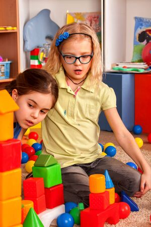 Children building blocks in kindergarten. Group kids playing toy on floor in interior preschool. Building a tower of cubes. Joint solution of assigned tasks. Stock Photo