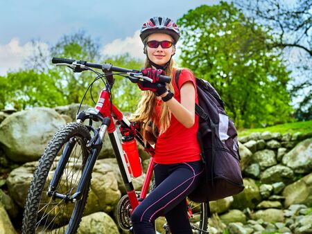 Woman on bicycle ride mountain. Girl traveling in summer park. Early morning with blue sky and clouds. Cycling person with rucksack . Sport trip is good for health. Trip on ecological route.