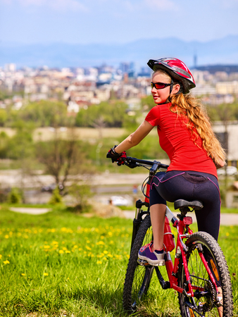 Escape urban . Bicycle girl has rest from city bustle. Woman wearing sport helmet returns home after hike in urbanization . Respect for environment. Back view. Return to civilization. Stock Photo