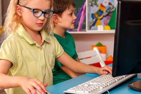 Children computer class us for education and video game. Kids in childrens club who spend many hours behind computer monitor harmful to health. Independent childrens creativity Stock Photo