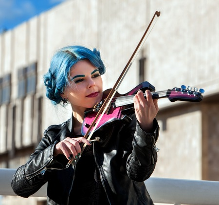 Woman perform music on violin in park outdoor. Girl with blue hairstyle performing jazz on city street . Spring outside city building background. Favorite female hobby. Stock Photo