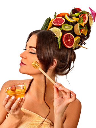 Honey facial mask with fresh fruits for hair and skin on woman head. Medical properties of honey concept. Popular masks for face. Honey softens skin. Stock Photo