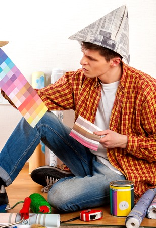 quandary: Repair home man holding paint bank. Tired and frustrated mad male in newspaper cap renovation apartment. Worker-builder student with color guide. Choice materials for construction he was in quandary