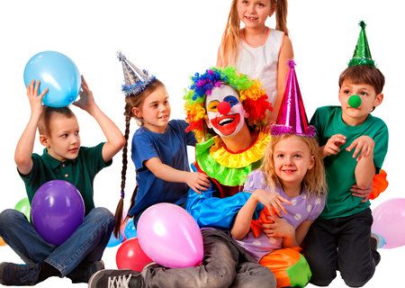 prank: Birthday child clown playing with children . Kid wearing party hat hold balloons happiest birthday. Fun of group people pose for camera on white background. Holiday for children in kindergarten. Stock Photo