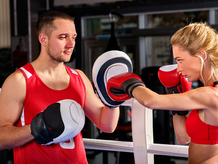 Boxing workout woman in fitness class ring. Sport box exercise two people. Man trainer holding sport mitts in gym. Female box gloves are red backview. Exercise in pairs.