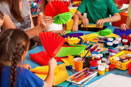 Schoolkinderen met een schaar in kinderen handen snijden papier met leraar in de klas. Ontwikkeling en sociale verdieping. Bijgesneden schot van grote groep meisjes en jongens samen. Stockfoto