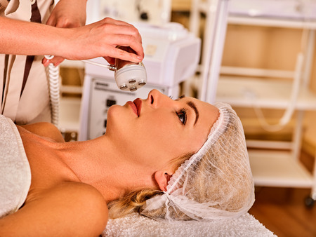 Woman receiving electric lift massage at spa salon.