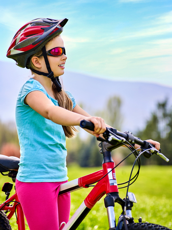 Child in helmet road bike for running on green grass against blue sky with white clouds. Stock Photo