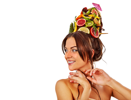 Hair mask from fresh fruits on woman head. Portrait of girl with beautiful face and hairstyle in spring flowers girl touch her skin as symbol lifestyle and beauty on isolated. Model advertises spa salon