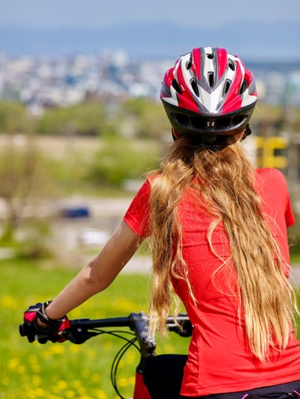 road bike: Bicycle girl has rest. Woman wearing sport helmet rides returns into city. Cycling is good for health. Cyclist is looking at city in distance. Person is traveling and dreaming.