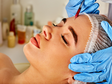 Filler injection for female forehead face. Plastic aesthetic facial surgery in beauty clinic. Stock Photo