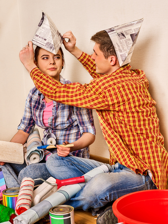 Repair family by happy couple building home . Woman and man in newspaper cap renovation apartment. Newlyweds together make repairs in their apartment. Stock Photo