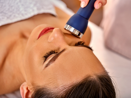Ultrasonic facial treatment on ultrasound face machine. Woman has electric lift massage spa salon. Stimulation muscles. Professional equipment microcurrent therapy in hand. How to preserve youth idea. Stock Photo