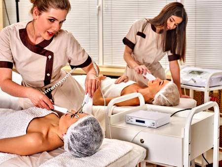 Couple facial massage beauty salon. Electric stimulation two women skin care . Equipment microcurrent lift face for family. Anti aging rejuvenation and non surgical treatment for group people. Stock Photo