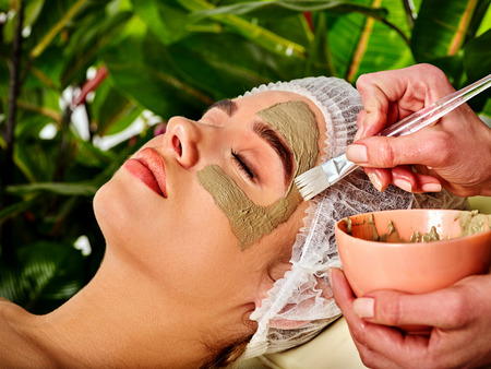 Mud facial mask of woman in spa salon. Massage with clay full face. Girl wearing medical hat on with therapy room. Female lying wooden spa bed. Mask made of healing clay. Green plant background.
