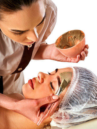 Mud facial mask of woman in spa salon. Massage with clay full face. Girl on with therapy room. Female lying wooden spa bed. Mud mask for moisturizing the skin. Stock Photo