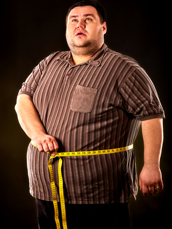 junk: Man belly fat with tape measure weight loss around body on black background. First day of diet. Person is obese on dark background.