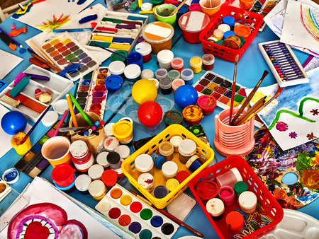furniture design: Kindergarten tables with painting brush. Preschool class waiting kids. Playroom with objects on table. Top view for art room. Materials for creative handwork. All for childrens creativity still-life.