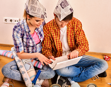 Repair family by happy couple building home using white laptop. Woman and man in newspaper cap renovation apartment. Purchase of furniture through the Internet.