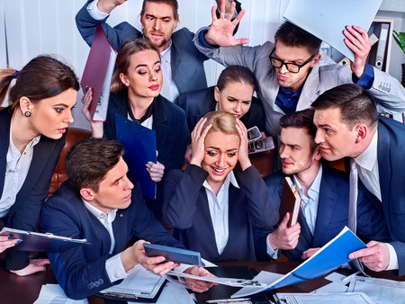 Mad business people office. Team people are unhappy with their leader. Intern woman manager holds ones hands by head does not cope with his duties. Crazy crowd in stress throw up chiefs papers.