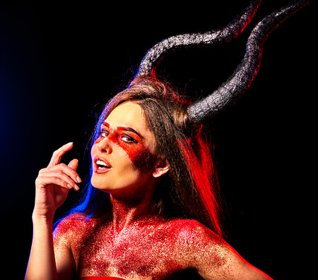 Mad satan woman on black magic ritual of hell. Witch with horns reincarnation mythical creature Sabbath. Halloween dark background. Zodiac Capricorn Aries. Make-up for night club for demon . Stock Photo