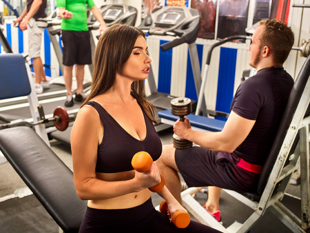 heavy: Woman holding dumbbell workout at gym. Girl with bare belly. Friends men with heavy dumbbells on background. Barbell in background number one. Female loves to train with dumbbells. Stock Photo
