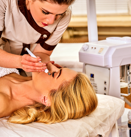 Facial massage at beauty salon. Electric stimulation skin care of woman. Professional equipment for microcurrent lift face without surgery number one . Non surgical treatment for preserve youth. Stock Photo