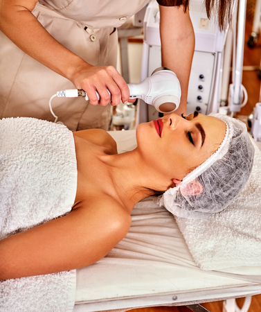 specials: Ultrasonic facial treatment on ultrasound face machine. Woman receiving electric lift massage at spa salon. Electronic stimulation female muscles microcurrent therapy . Technologies of rejuvenation.