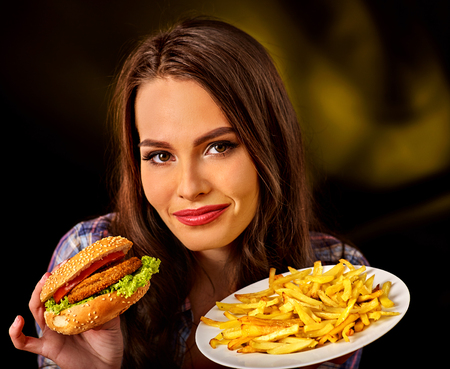 Woman eating french fries and hamburger. Student consume fast food on table. Advertise fast food on dark background. Use of semi-finished products because of unwillingness to cook. Stock Photo