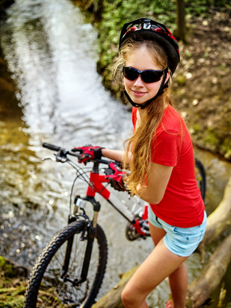 Bicycle teen with ladies bikes in summer park. Womens road bike for running on nature. Girl cycling fording throught water. Cycling trip is good for health. Girl is traveling alone. Stock Photo