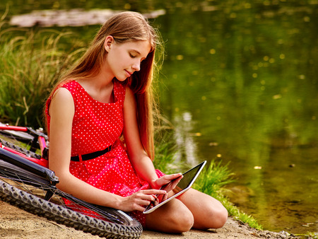 Bikes cycling girl wearing red polka dots dress recreation near bicycle into park. Children watch tablet pc in ecotourism. Femle went into social network in campaign. First love. Stock Photo