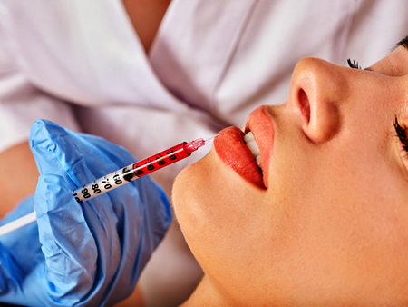 Filler injection for female forehead face. Plastic aesthetic facial surgery in beauty clinic. Silicone lips. Doctor in medical gloves with syringe injects lips augmentation. Preservation of youth. Stock Photo