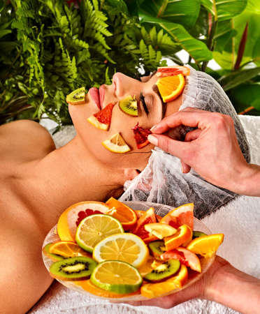 Facial mask from fresh fruits for woman . Beautician apply slices of avocado, grapefruit and kiwi Girl in medical hat lying on spa bed for skin care procedure in salon. Woman is resting in a spa salon Stock Photo