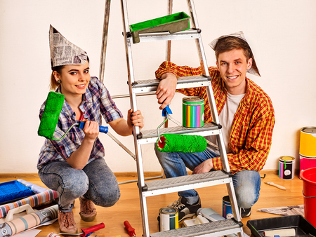 Repair family by happy couple building home using ladder. Woman and man in newspaper cap renovation apartment. Stock Photo