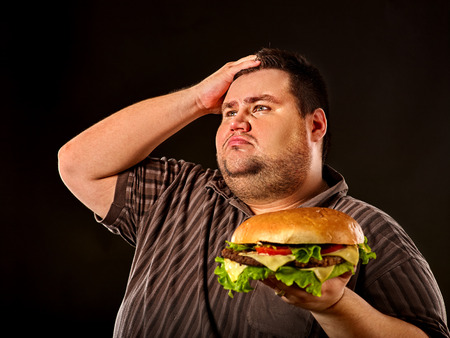 Man eating fast food hamberger. Fat person made great huge hamburger and admires him, intending to eat it. Junk meal leads to obesity. He is tormented by his conscience about the failure of the diet. Stock Photo