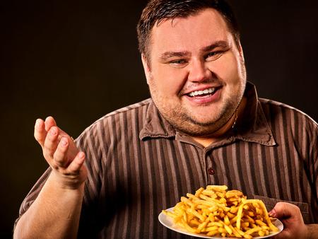 Difficoltà di dieta dell'uomo grasso che mangia fast food. Paziente in sovrappeso che ha viziato il cibo sano mangiando patatine fritte. Il pasto di spazzatura porta all'obesità. Pubblicizzare patate fritte. Archivio Fotografico - 82338719