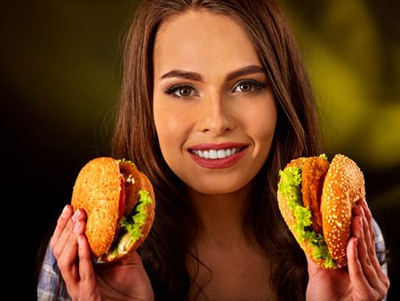 school cafeteria: Woman eating hamburger. Student consume fast food. Girl holding two small burger . Girl trying to eat a lot of junk. Advertise fast food on black background.