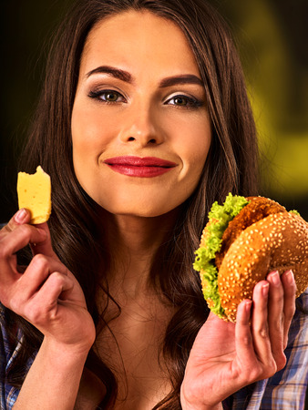 beefburger: Woman eating a hamburger.